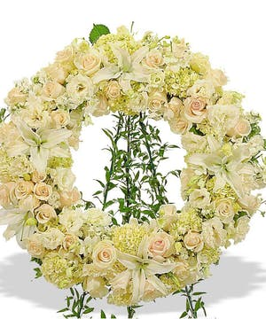All white floral heart wreath presented on an easel.