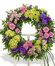 Peaceful lavenders, blues and greens are featured in this traditional wreath presented on an easel.